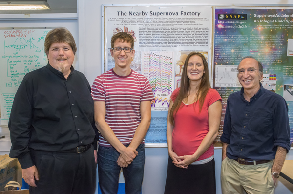 From left, Greg Aldering, Kyle Boone, Hannah Fakhouri and Saul Perlmutter of the Nearby Supernova Factory. Behind them is a poster of a supernova spectrum. Matching such spectra can double the accuracy of distance measurements. (Photo by Roy Kaltschmidt/Berkeley Lab)